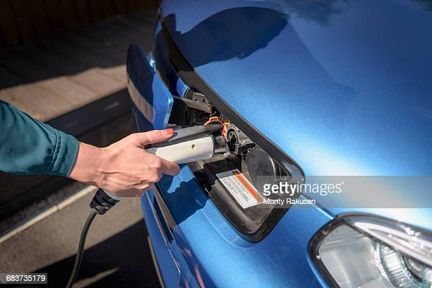 Woman charging electric car from charging point, close up detail