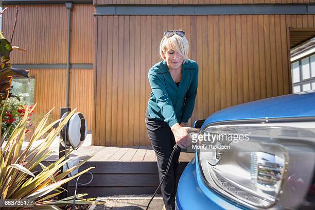 woman charging electric car from charging point - elektroauto stock-fotos und bilder