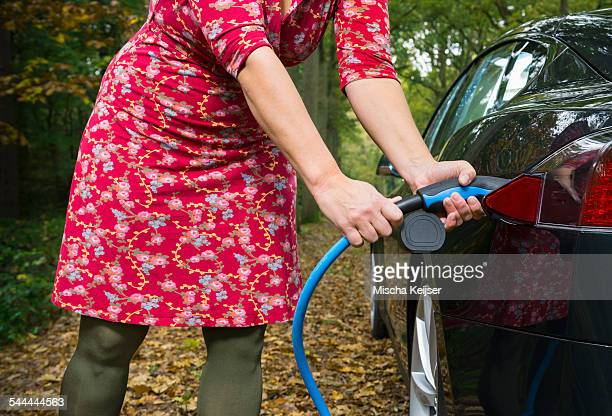Woman charging electric car in forest