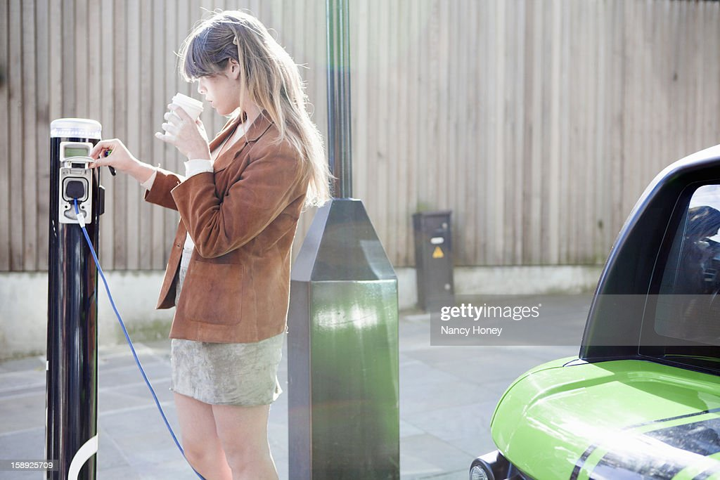 Woman charging electric car on street : Stock Photo