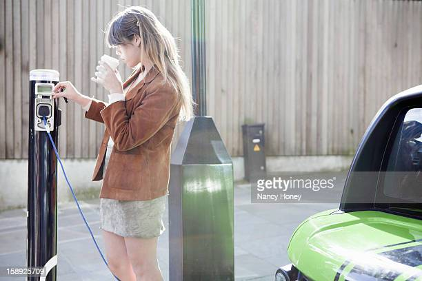 woman charging electric car on street - elektroauto stock-fotos und bilder