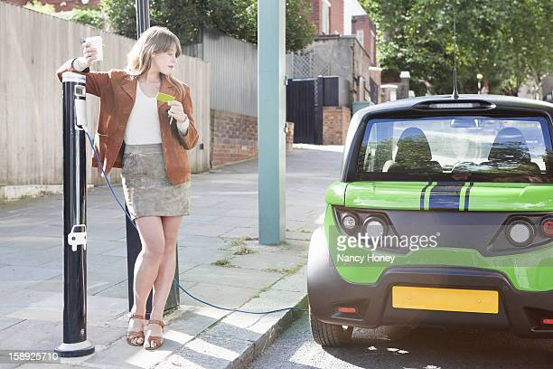 woman charging electric car on street - nancy green stock pictures, royalty-free photos & images