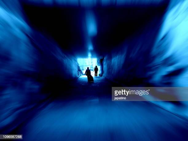 woman chased by a man in a dark tunnel - 性的暴行 ストックフォトと画像