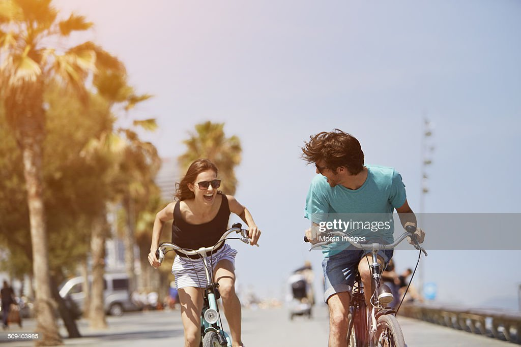 Woman chasing man while riding bicycle : Foto de stock