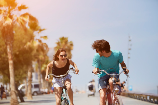 Woman chasing man while riding bicycle 509403985