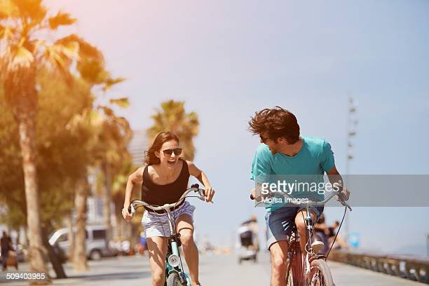woman chasing man while riding bicycle - fietsen stockfoto's en -beelden