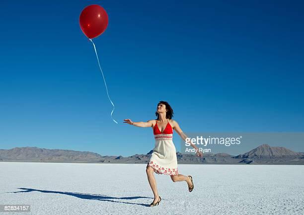 woman chasing red balloon in desert - 追いかける ストックフォトと画像