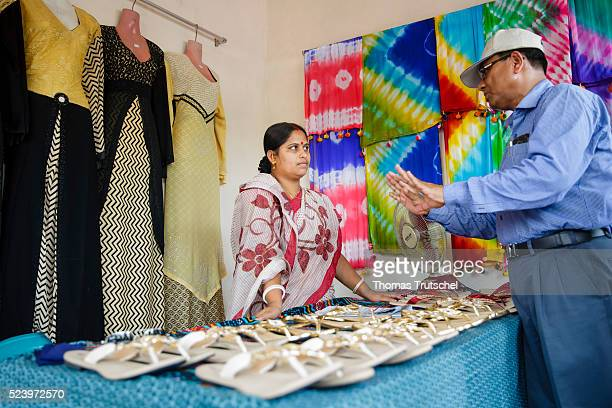 Woman chats in her own shop on a countryside market with a man on April 10, 2016 in Narikelbari, Bangladesh.