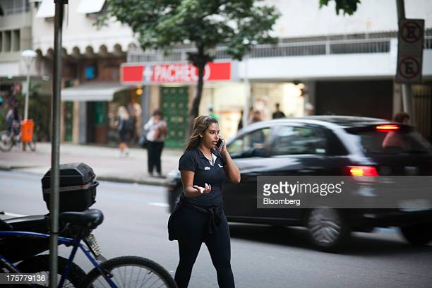 A woman chats on her mobile phone in the Ipanema neighborhood of Rio de Janeiro Brazil on Tuesday Aug 6 2013 Telefonica Brasil SAs Vivo now...