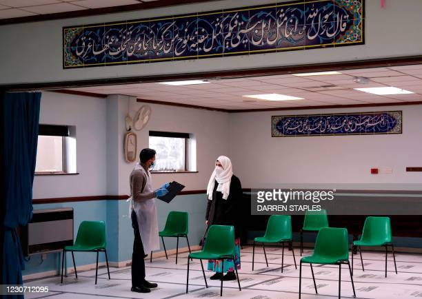 Woman chats with a medical worker prior to receiving the Oxford/AstraZeneca Covid-19 vaccine at the Al-Abbas Islamic Centre, which has been converted...