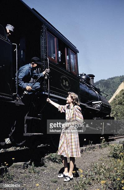 A woman chats with the engineers of the vintage narrow guage steam engine on the East Tennessee Western North Carolina railway running the 65 miles...