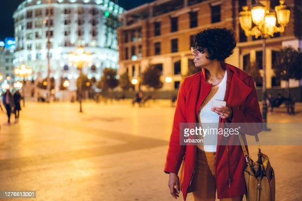 woman chatting online on phone on town square - skopje stock pictures, royalty-free photos & images