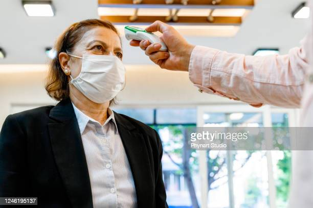 woman checked with thermometer to control the temperature required to be checked in quarantine - visita imagens e fotografias de stock