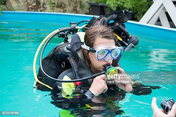 Woman Checking Aqualung In Swimming Pool