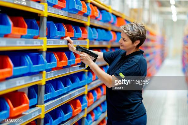 woman checking barcodes in warehouse - industrial storage bins stock pictures, royalty-free photos & images