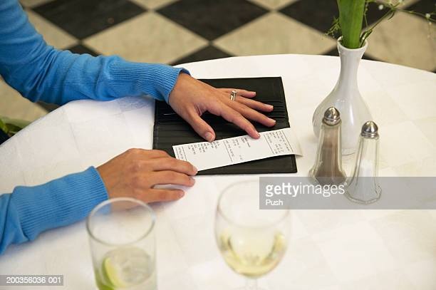 Woman checking bill in restaurant, close-up