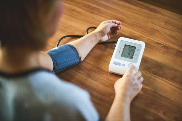 woman checking blood pressure - high blood pressure stock pictures, royalty-free photos & images