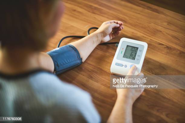 woman checking blood pressure - blood pressure gauge stock pictures, royalty-free photos & images