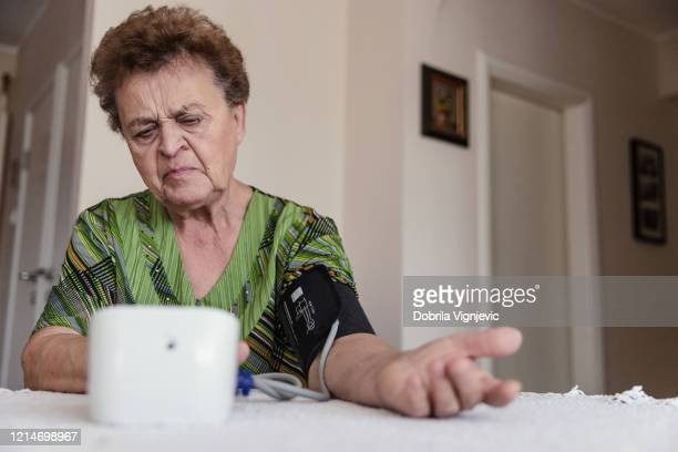 woman checking blood pressure - heart disease stock pictures, royalty-free photos & images