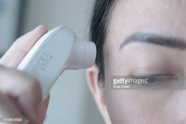 woman checking body temperature of covid-19 coronavirus treatment in quarantine - prevention stock pictures, royalty-free photos & images