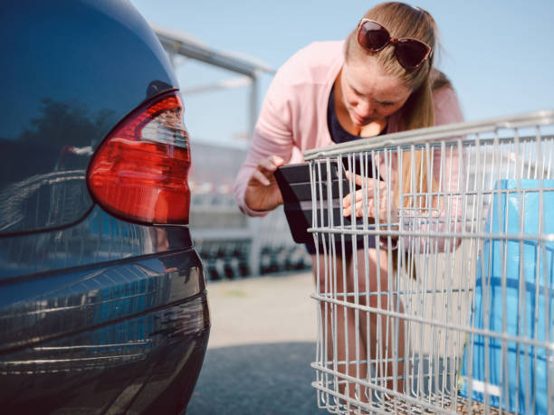 Woman checking car after car accident at supermarket.