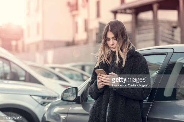 woman checking cell phone - winter coat stock pictures, royalty-free photos & images
