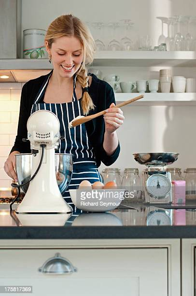 Woman checking consistency of cake mixture