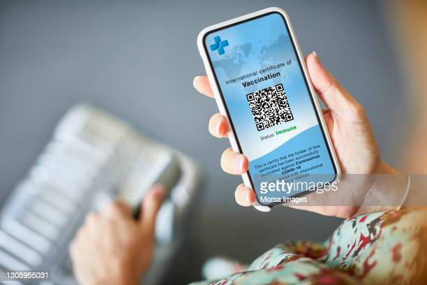 woman checking covid-19 vaccine passport on cellphone - airport stock pictures, royalty-free photos & images