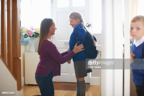 woman checking daughters school uniform in hallway - first day of school stock pictures, royalty-free photos & images