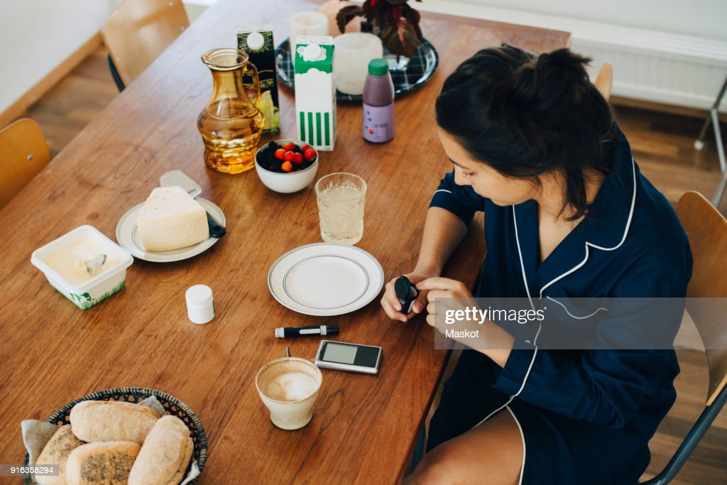 Woman checking diabetes while having breakfast on table at home : Stock Photo