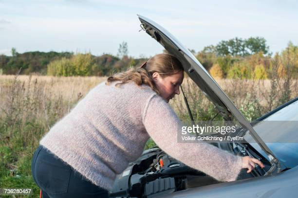 Woman Checking Engine Of Broken Down Car Against Field