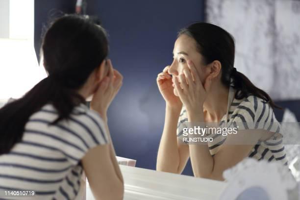 woman checking face in mirror - しわ ストックフォトと画像