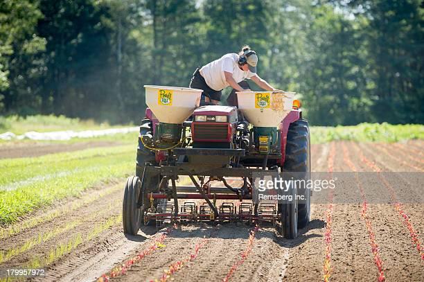 CONTENT] Woman checking fertilizer equipment on tractor Brunswick Maine