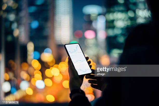 woman checking financial stock market analysis on smartphone in city, with illuminated city street light and urban skyscrapers as background at night - prosperity stock pictures, royalty-free photos & images