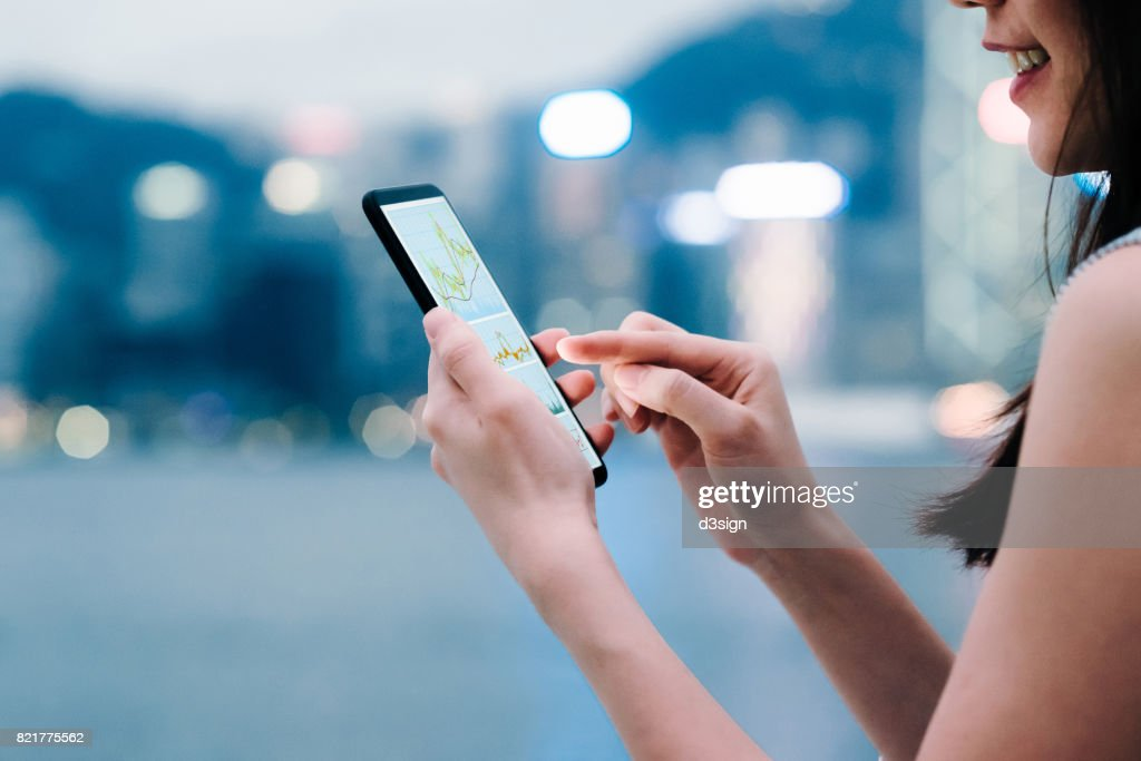 Woman checking financial trading data with smartphone in city : Stock Photo