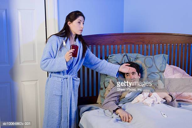 Woman checking forehead of man lying in bed