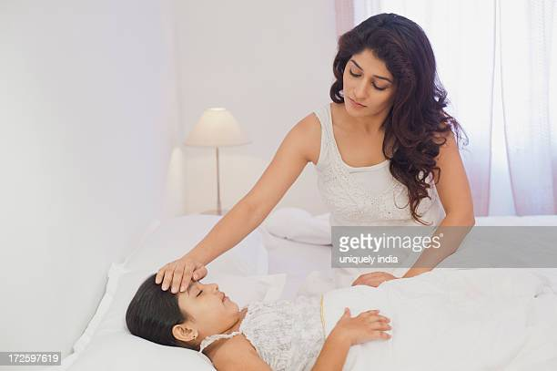 Woman checking her daughter temperature