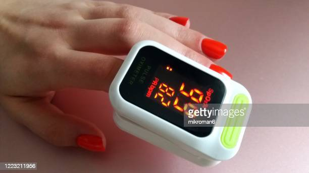 a woman checking her heart rate and oxygenation level on her finger - pulse oximeter stock pictures, royalty-free photos & images
