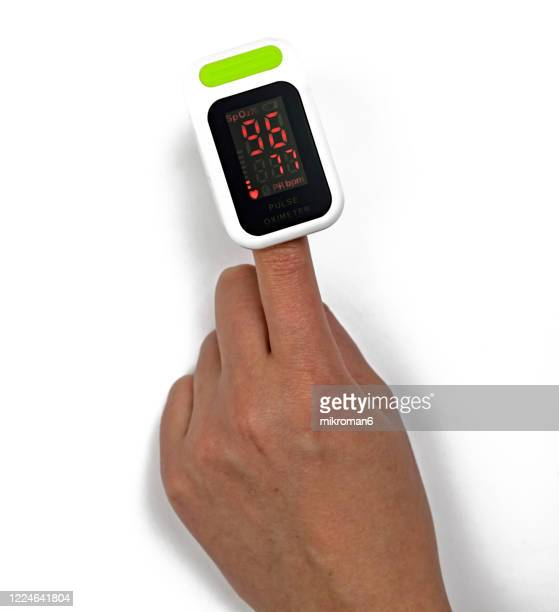a woman checking her heart rate and oxygenation level on her finger - cardiac conduction system stock pictures, royalty-free photos & images