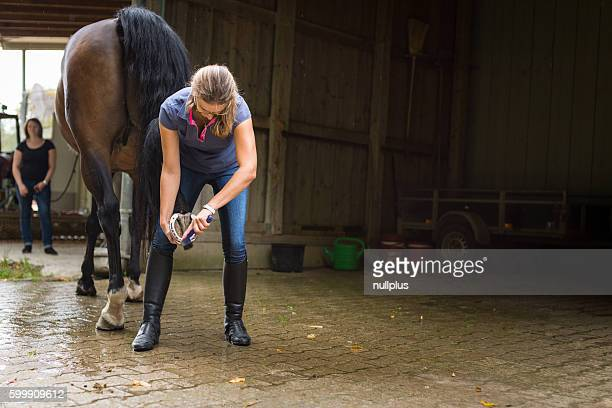 Woman checking her horse's hooves