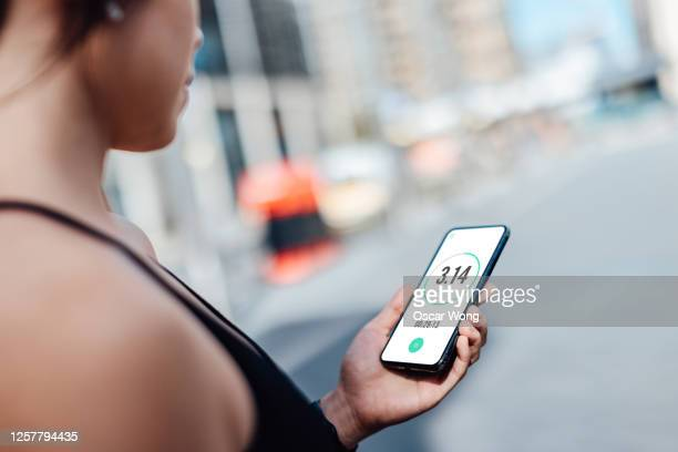 woman checking her mobile phone after run - looking over shoulder stock pictures, royalty-free photos & images