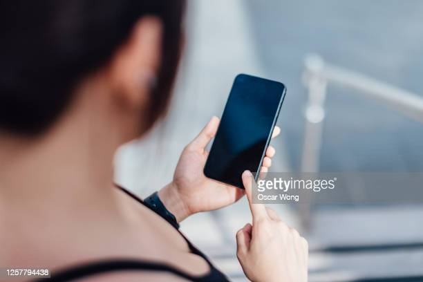 woman checking her mobile phone before exercising - looking over shoulder stock pictures, royalty-free photos & images