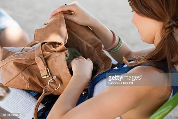 woman checking her purse, paris, ile-de-france, france - clutch bag stock pictures, royalty-free photos & images