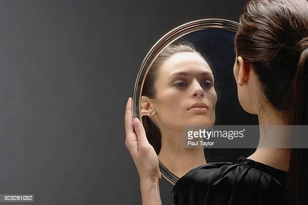 woman checking her reflection in silver serving platter - specchio foto e immagini stock