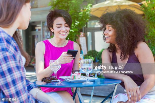 Woman checking her smart phone at an outdoor cafe