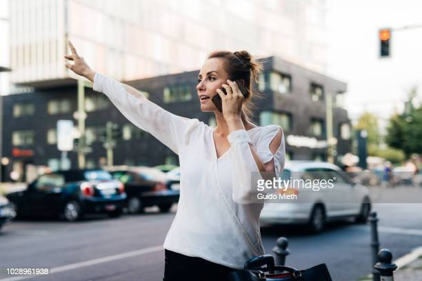 Woman checking her smart phone while waiting for taxi.