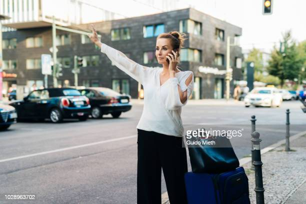 Woman checking her smart phone while waiting for Uber.