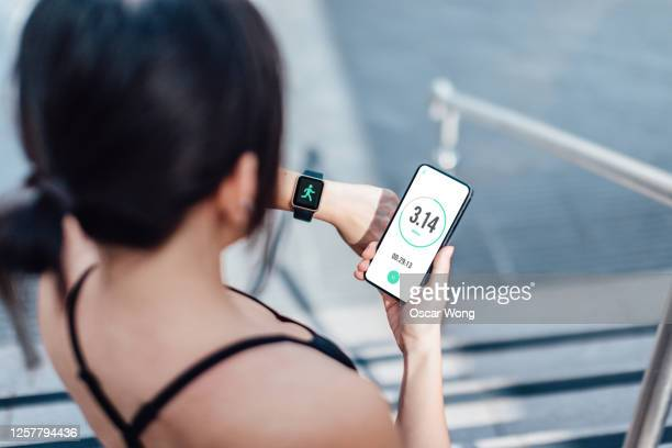 woman checking her smart watch and mobile phone after run - medical equipment stock pictures, royalty-free photos & images