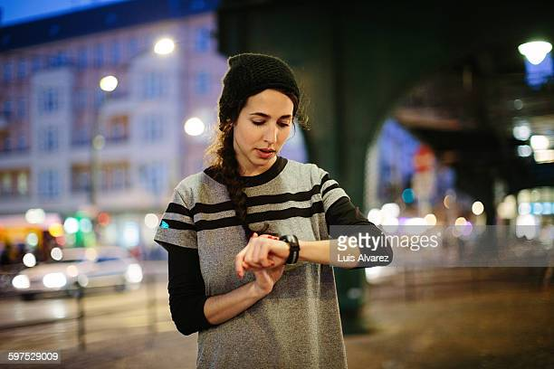 Woman checking her smart watch in city