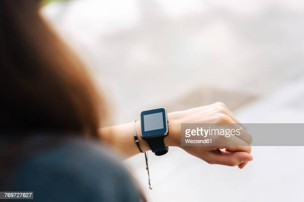 woman checking her smartwatch - wrist stock pictures, royalty-free photos & images